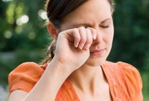 Женщина чешет правый глаз